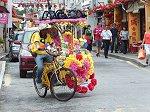 ジョンカーストリートを流す花飾りの観光人力車トライショー