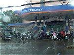 突然のスコールに雨宿りするバイク